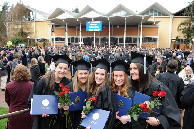 Five smiling students holding diplomas at commencement ceremony