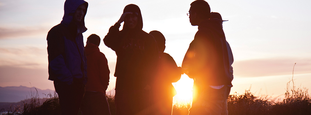 Five students standing in a circle silhouetted by a settting sun