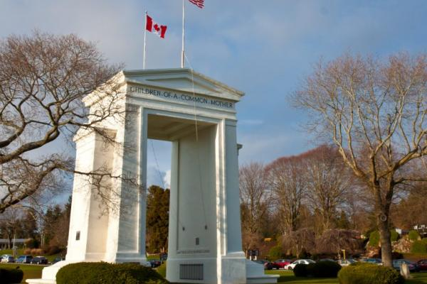"The Peace Arch, a large white arch with the words ""Children of a common mother"" engraved on it along with flying US and Canadian flags atop, stands proudly at the US/Canada Border in Blaine, WA"