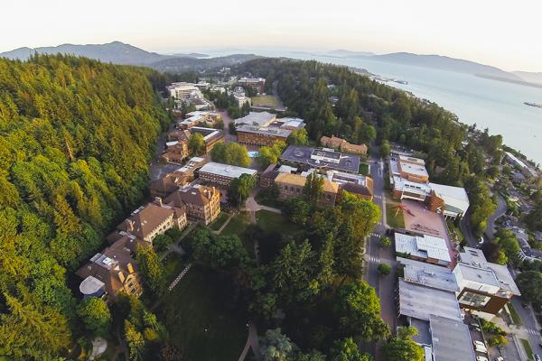 Aerial view of campus nestled against Sehome Hill Arboretum. You can see the mountains, bay, and islands surrounding Bellingham.