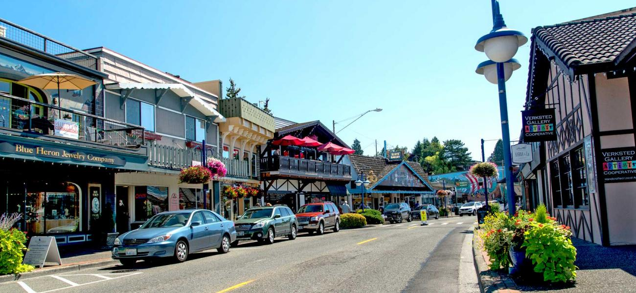A shot of the quaint small shops of downtown Poulsbo. The streets are lined with with cars on this sunny, blue sky day.